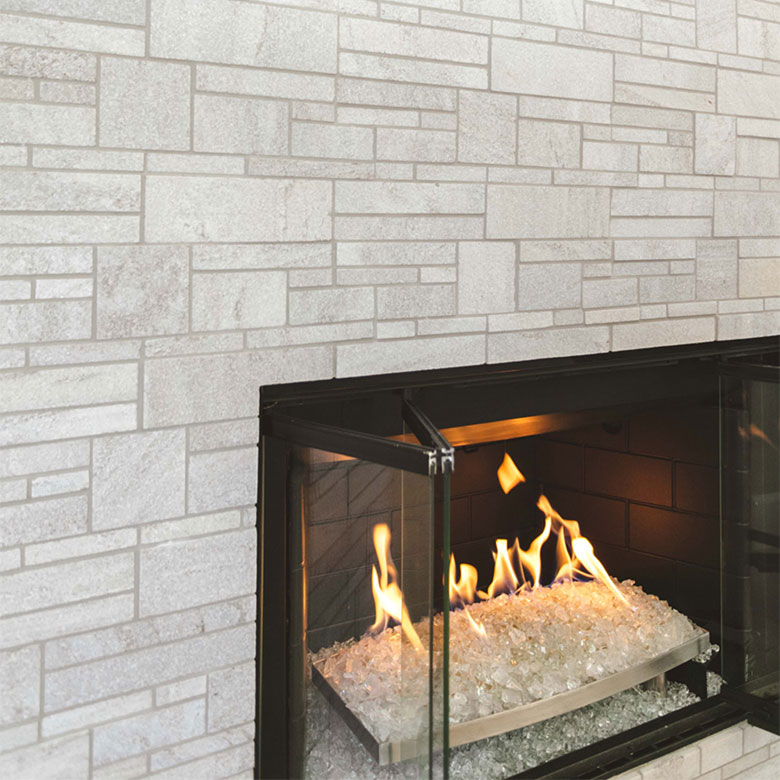 Fireplace with burning logs surrounded by white tile
